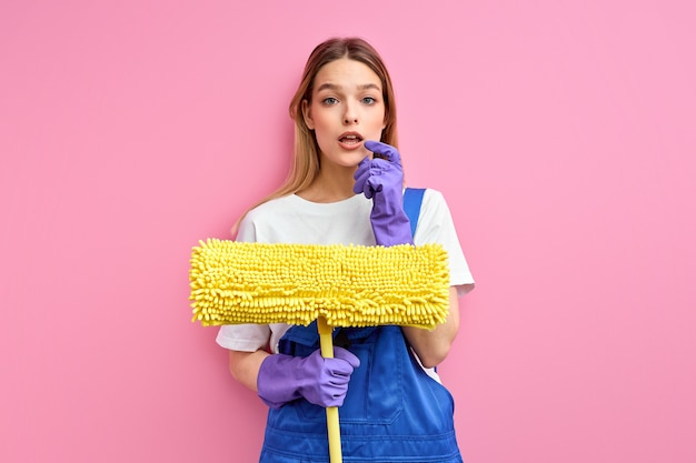 Schonere vrouw die handschoenen draagt die zwabber over geïsoleerde roze achtergrond houden ernstig gezicht denken over vraag, zeer verward idee.