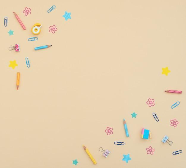 School- en kantoorbenodigdheden potloden, clips, notitiepapier, stickers, vlakgom op gele achtergrond.