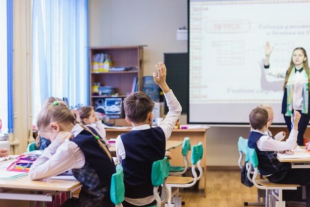 School en studenten, het kind stak zijn hand op om de leraar, vriendschap te beantwoorden