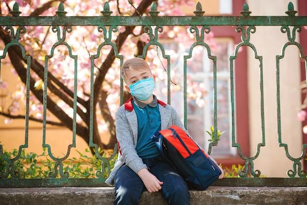 School gesloten. droevige jongen met rugzak dichtbij schoolomheining. schoolkid met veiligheidsmasker. medisch masker om coronavirus te voorkomen.