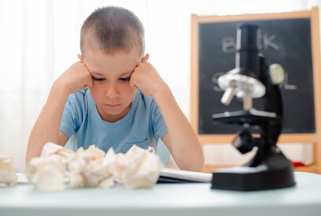School jongen zit thuis klaslokaal liggend bureau gevuld met