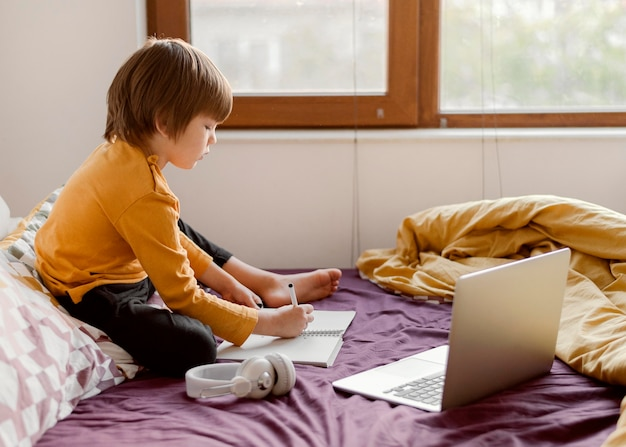 School jongen zittend in bed met laptop en koptelefoon