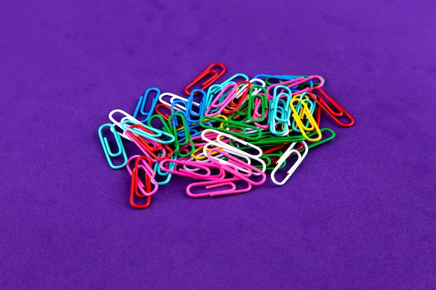 School kantoorbehoeften gekleurde paperclips geïsoleerd op paars
