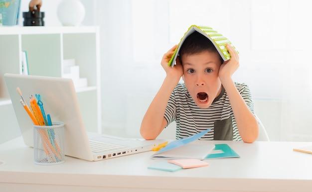 School kind jongen zit aan bureau leren verstopt achter studie notitieboekje geweldig nieuws hoogste cijfer met succes examens test school, huiswerk volbrengen blij opgewonden geschrokken