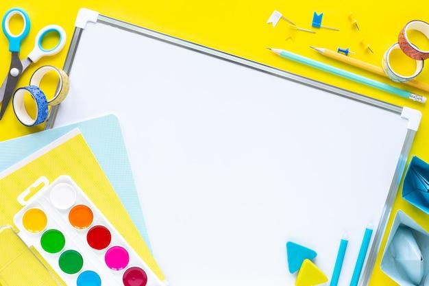 School kleurrijke kantoorbehoeften op geel met copyspace