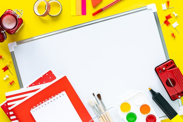 School kleurrijke kantoorbehoeften op gele achtergrond met copyspace.