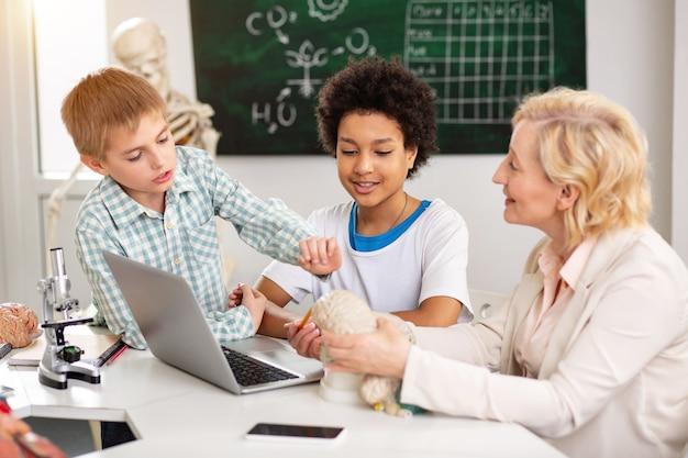 School les. vrolijke positieve leraar die met haar student praat terwijl hij hen het materiaal uitlegt