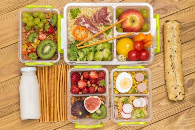School lunchbox met set van fruit, bessen, groenten en ham