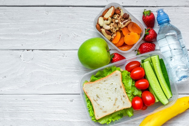 School lunchboxen met sandwich en verse groenten, fles water, noten en fruit