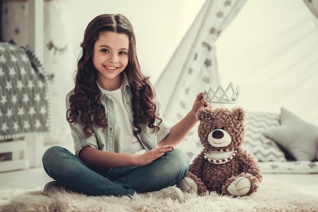 School meisje speelt met een teddybeer, camera kijken.