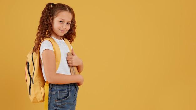 School meisje staande zijaanzicht kopie ruimte