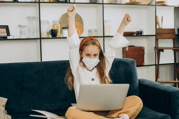 School meisje studeren thuis dragen masker, leren op afstand