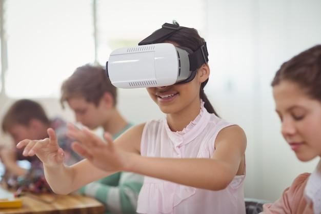 School meisje zit in de klas met behulp van virtual reality headset