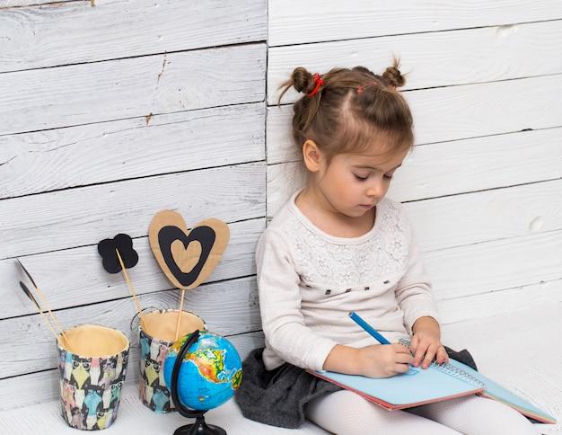 School meisje zit op een witte houten met een wereldbol in zijn handen en een notebook
