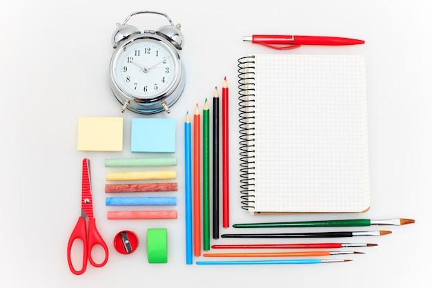 School met notitieboekjes, potloden, borstel, schaar en appel op wit wordt geplaatst dat