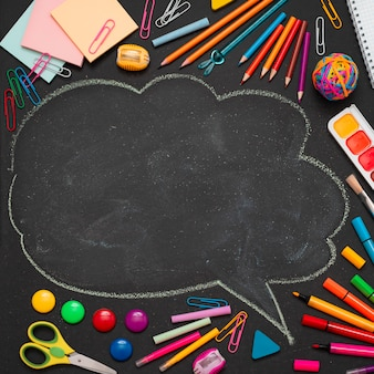 School multi-gekleurde benodigdheden, potloden en een getekende wolk met kopie ruimte voor tekst.