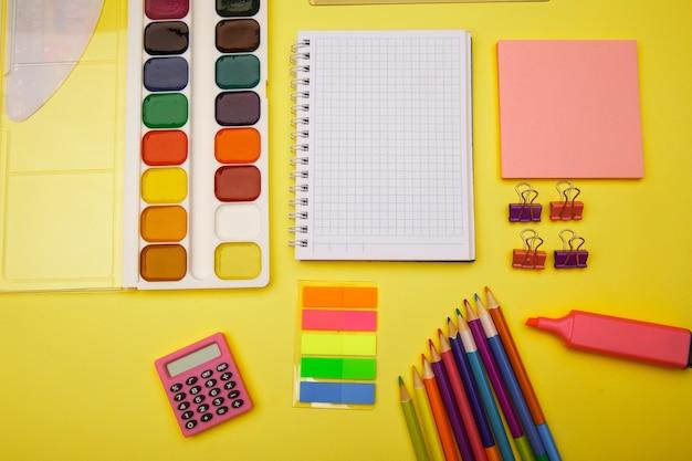 School notebook en briefpapier over gele tafel. terug naar school abstracte achtergrond