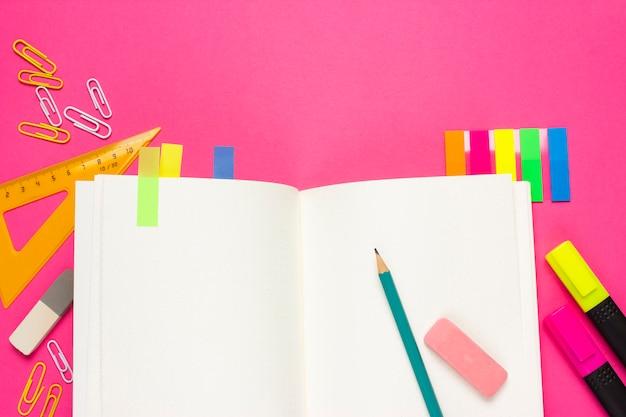 School of student levert op een roze achtergrond. terug naar school. notebook, potlood, gum, liniaal, markeringen, paperclips