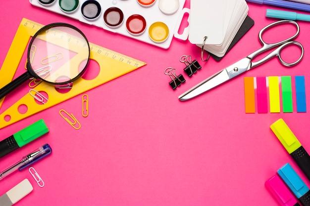 School of student levert op een roze achtergrond. terug naar school. potlood, gum, liniaal, stiften, paperclips, schaar, verf