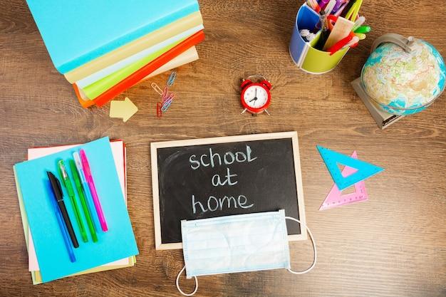 School thuis inscriptie met krijt op een klein schoolbord. bureau met schoolaccessoires en een beschermend masker, bovenaanzicht, flat lay