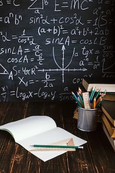 Schoolbank in de klas, met boeken op de achtergrond van krijt bord met schriftelijke formules