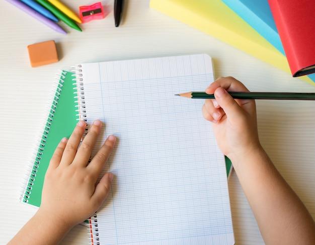 Schoolbankachtergrond die met kinderenhanden een potlood houden