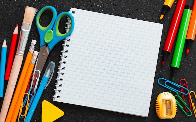 Schoolbenodigdheden bovenaanzicht op de achtergrond van het schoolbord