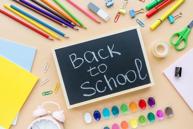 Schoolbenodigdheden briefpapier, kleurpotloden, verf, papier op oranje