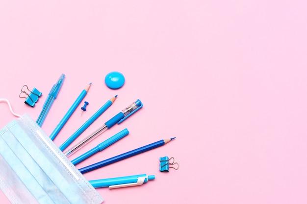Schoolbenodigdheden en covid-preventiehulpmiddelen terug naar school tijdens het pandemische concept op een roze ba...