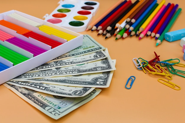 Schoolbenodigdheden en dollars. concept is om kantoorbehoeftenvoorwerpen te kopen.