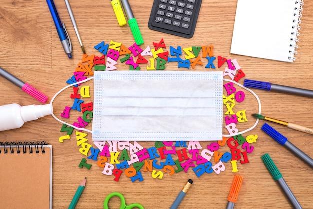 Schoolbenodigdheden en kleurrijke letters rond gezichtsmasker in het midden op houten achtergrond