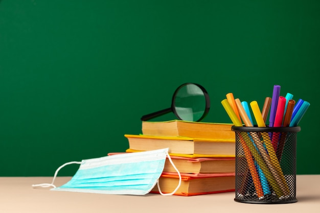Schoolbenodigdheden en medisch gezichtsmasker op bureau, exemplaarruimte