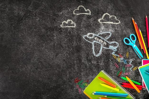 Schoolbenodigdheden en vliegtuigen geschilderd met krijt op bord