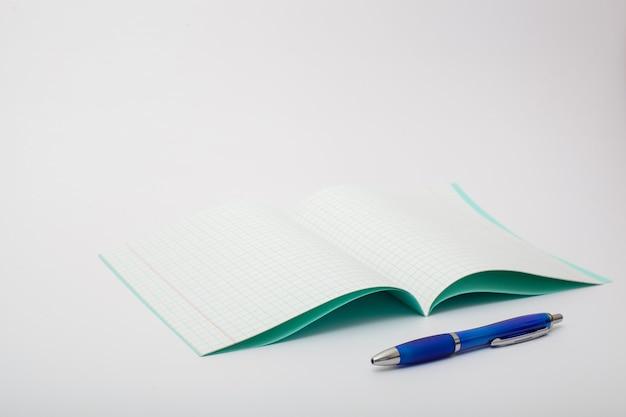 Schoolbenodigdheden geïsoleerd op een witte achtergrond. foto over het onderwerp studeren op school. notitieboekje en een blauwe balpen op een witte achtergrond