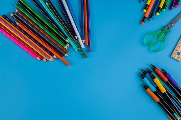 Schoolbenodigdheden, kleurpotloden bovenste rand op een blauwe achtergrond