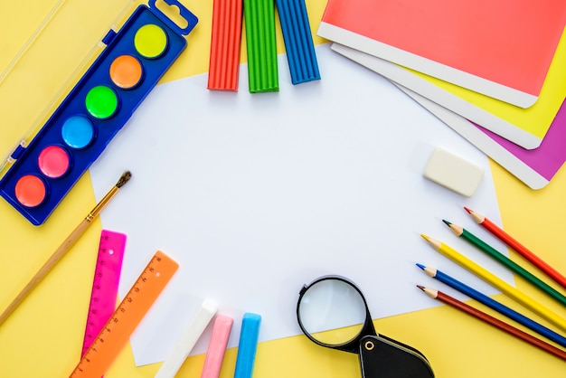 Schoolbenodigdheden met een stuk papier, bovenaanzicht