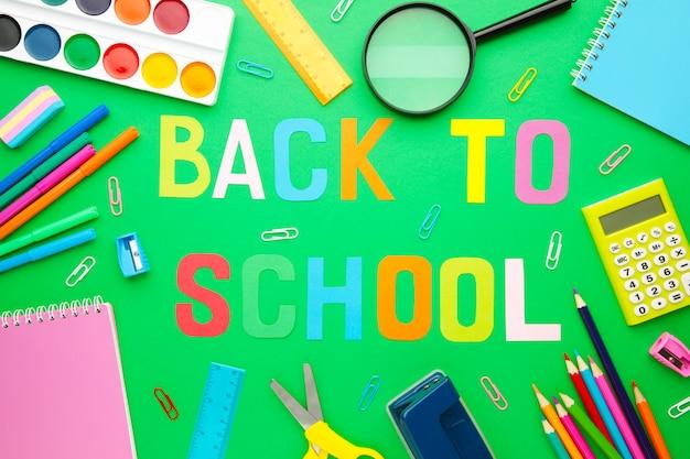 Schoolbenodigdheden met inscriptie terug naar school op groene muur