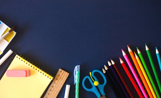 Schoolbenodigdheden op donkerblauw