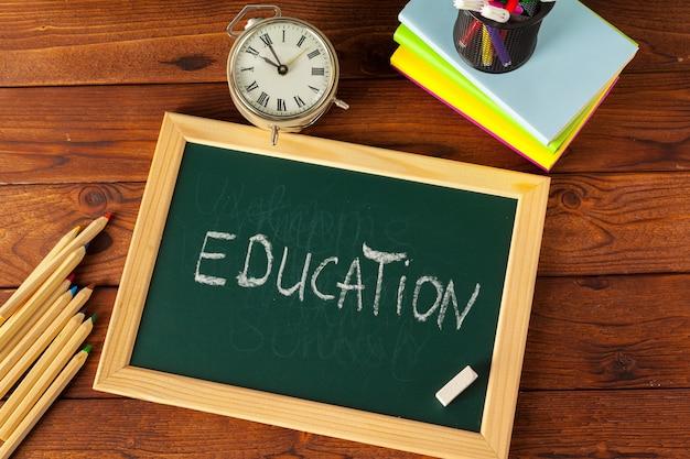 Schoolbenodigdheden op een houten tafel en schoolbord