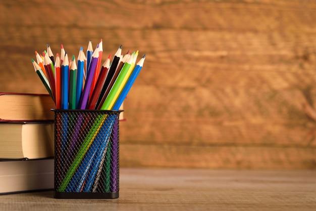 Schoolbenodigdheden op een warme, mooie houten achtergrond. gekleurde kinderpotloden in een kast met zwarte houder voor briefpapier.