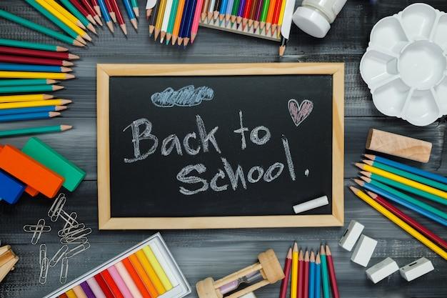 Schoolbenodigdheden op een zwarte bord. terug naar school-concept.