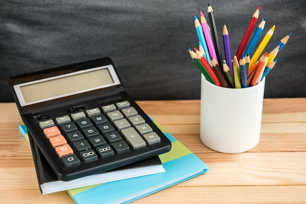 Schoolbenodigdheden op zwarte bord achtergrond. kleurpotloden, rekenmachine, regels en voorbeeldenboeken. terug naar school-concept.