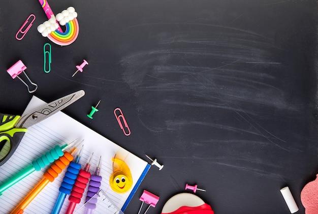 Schoolbenodigdheden op zwarte bord achtergrond met kopie ruimte, terug naar school