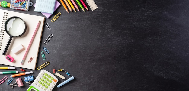 Schoolbenodigdheden op zwarte rugplank, terug naar schoolconcept