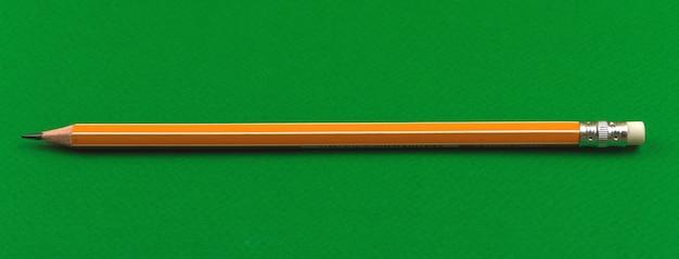 Schoolbenodigdheden, schoolgeel potlood met gum op een groene tafel, bannerfoto