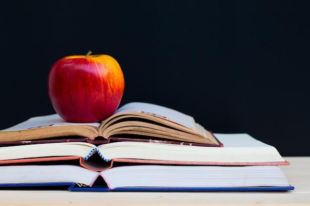 Schoolboeken en appel tegen bord