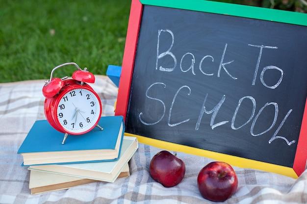 Schoolboeken met rode wekker en bord met terug naar schoolcitaat