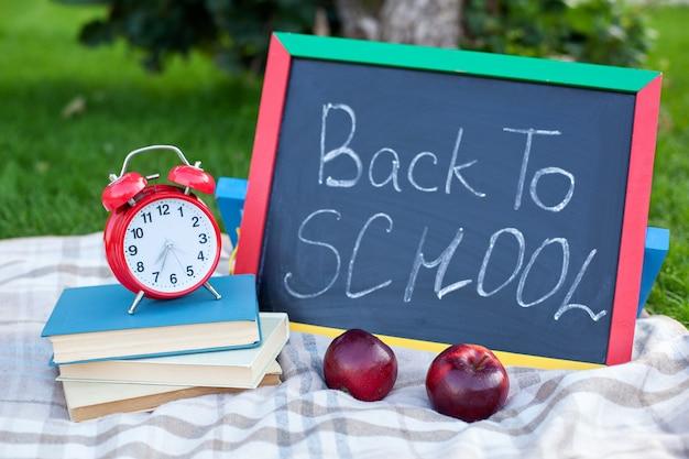 Schoolboeken met rode wekker op bord