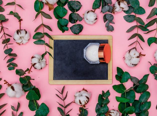 Schoolbord en lichaamsverzorgingscrème liggen op de roze tafel, rond de bladeren en takken van eucalyptus en katoen