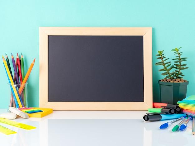 Schoolbord en schoolbenodigdheden op witte tafel door de blauwe muur. zijaanzicht, leeg